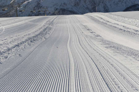 groomer: Fresh snow groomer tracks on a ski piste in the dolomites Stock Photo