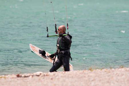 kitesurf: LAKE OF SANTA CROCE, ITALY - JULY 13, 2014: Kitesurfer launches his kite in the lake of Santa Croce