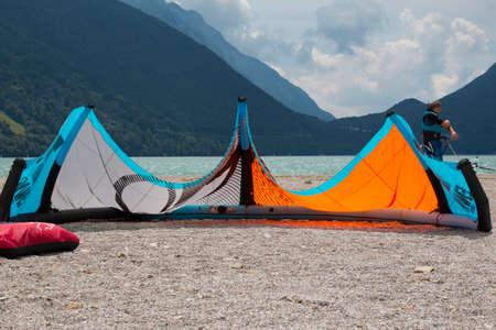 kitesurf: LAKE OF SANTA CROCE, ITALY - JULY 13, 2014: A surging kite lying on a beach in the lake of Santa Croce