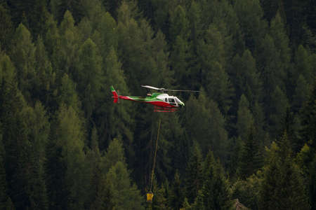 rescue helicopter: Falcade, Belluno, Italy - August 21, 2015: transport helicopter provides material for a construction site in the mountains