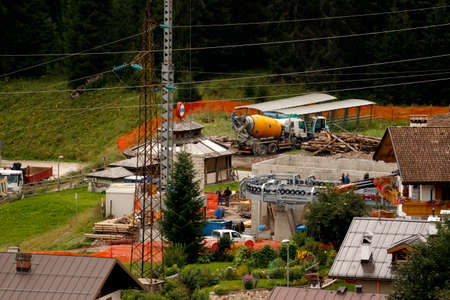 Ski Area: Falcade, Belluno, Italy - August 21, 2015: Cement mixer truck works at building site under construction the new modern cabin lift in the  ski area San Pellegrino