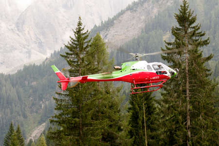 helicopter rescue: Falcade, Belluno, Italy - August 21, 2015: transport helicopter provides material for a construction site in the mountains