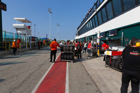 pneumatic tyres: Misano Adriatico, Italy - April 10, 2016:  A man pushes a rack of tyres at the Misano World Circuit, in Misano Adriatico, Italy, ahead of the Italian F4 Championship Powered by Abarth.