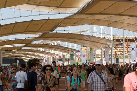 visitors: Milan, Italy, 12 August 2015: visitors walking under the tensile roof covering main walk at exhibition Expo 2015 Italy Editorial