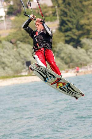 kitesurf: Lake Of Santa Croce, Italy – May 21, 2016: Professional  Kitesurfer jumps over the water during training on Lake of Santa Croce