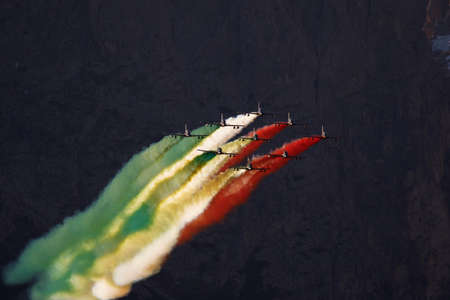 tricolour: Alta Badia, Italy 20 December 2015: Italian special unit airforce Frecce Tricolori (Tri-colour Arrows) spread smoke with the colours of the Italian flag during the Audi Fis Alpine Skiing World Cup Men's Giant Slalom Race. Editorial
