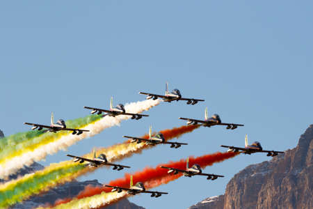 fis: Alta Badia, Italy 20 December 2015: Italian special unit airforce Frecce Tricolori (Tri-colour Arrows) spread smoke with the colours of the Italian flag during the Audi Fis Alpine Skiing World Cup Men's Giant Slalom Race. Editorial