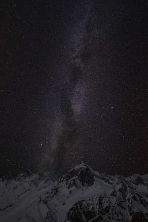 Mountain peaks in the background of the milky way. Night landscape with starry sky