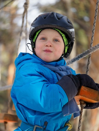 A little boy (6 years old) mountaineering in the winter in a children's rope town Zdjęcie Seryjne