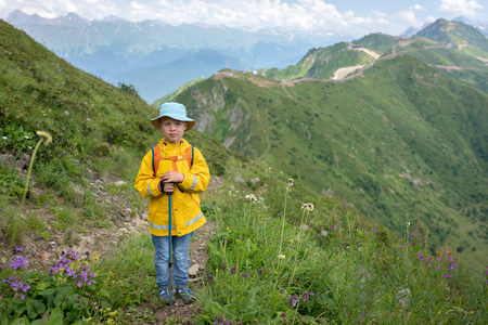 A boy traveler with trekking poles in a yellow raincoat and a panama is standing on the path to the top of the mountain range. Caucasus, Russia Foto de archivo