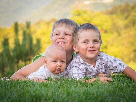 The three brothers are lying on a green lawn. Emotions of children. Vacation with children. Childcare. Goods for kids. Sun protection. Child development.