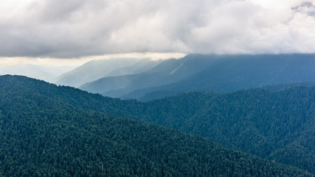 The Valley between the mountains covered with forests in dense fog. Array Chugush 3237 m on the right disappeared in the clouds. Background of mountain ranges one after another. Travel background Stock Photo