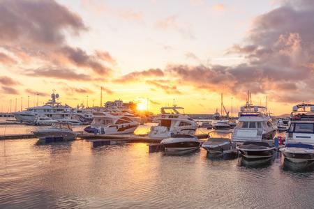 Schöner orangefarbener Sonnenuntergang im Seehafen mit festgemachten Yachten. Sonnenuntergang über dem Seepier mit Yachten und Booten. Orangefarbener Sonnenuntergang im Meer. Sotschi, Russland.