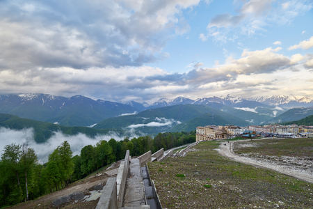 Ski resort in the spring against the backdrop of snowy mountains on a cloudy day. Snowy mountains in the fog. Krasnaya Polyana, Sochi, Russia Stok Fotoğraf