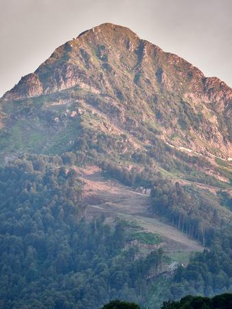 Grüner Berghang mit Seilbahnen und Skipisten bei bewölktem Sommersonnenuntergang. Schwarze Pyramide, Krasnaya Polyana, Sotschi, Kaukasus, Russland