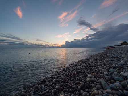 A beautiful pink sunset on a pebble beach. The rays of the setting sun pass through the clouds. The sun disappeared over the sea.
