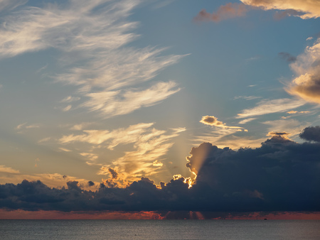 Beautiful yellow-pink sunset in the clouds over the sea. The rays of the setting sun pass through the clouds. The sun disappeared behind the clouds. Banco de Imagens