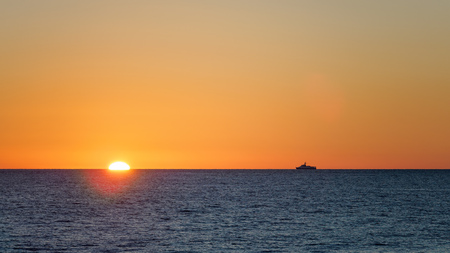 Orange sunset over the sea. Lonely ship on the horizon. The sun hides behind the horizon in the sea. Stock Photo