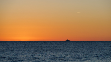 Orange sunset over the sea. Lonely ship on the horizon. The sun hides behind the horizon in the sea. Banco de Imagens