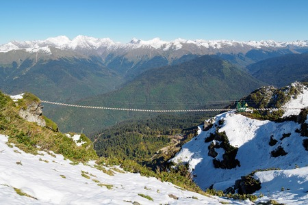 Suspended pedestrian bridge in the high snowy mountains. Clear blue sky. Mountains with green slopes. Archivio Fotografico