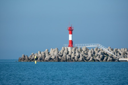 Lighthouse on a breakwater in the blue sea on a clear sunny day. Stok Fotoğraf