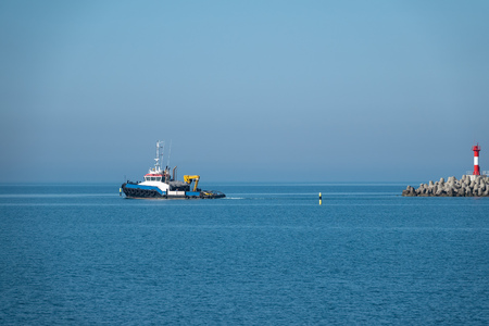 The sea tug comes out of the harbor next to the lighthouse. Sea harbor on a sunny day.
