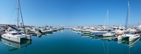 Sea pier with several rows of yachts and boats