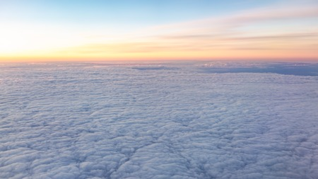 Beautiful pink sunrise over the clouds. View of the dawn in the clouds from the plane.