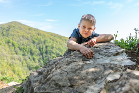 A boy traveler climbed to the top of a cliff surrounded by a green mountains with forest.