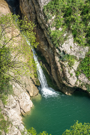 The view from the height of the lake with a high waterfall falling into it. Waterfall in a mountain gorge. Stok Fotoğraf