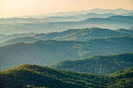 Layers of green mountains and hills in the haze during sunset. Beautiful sunset in the mountains. Beautiful sunset in a hilly valley with villages and fog in the lowlands.