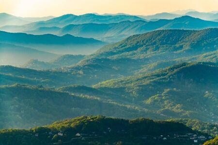 Capas de verdes montañas y colinas en la bruma durante la puesta de sol. Hermoso atardecer en las montañas. Hermoso atardecer en un valle montañoso con pueblos y niebla en las tierras bajas. Foto de archivo