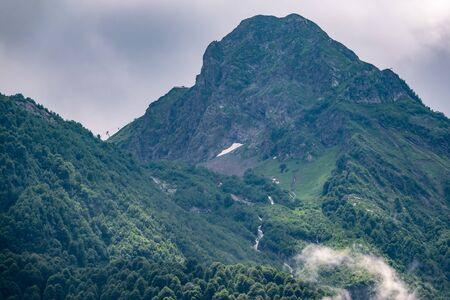 Grüne Hänge und felsige Gipfel des Hochgebirges an bewölkten Sommertagen. Sommer oder Frühling in den Bergen.