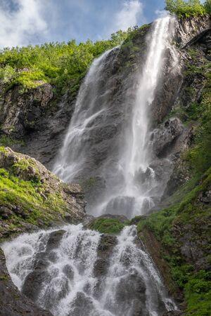 Im Frühling oder Sommer fällt ein hoher Wasserfall von einer Klippe. Mächtiger Strom eines Gebirgsflusses zwischen Steinen und Felsen.