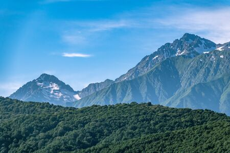 High mountains with green slopes and snowy peaks. Mountain ranges in summer. Stock Photo - 128520709