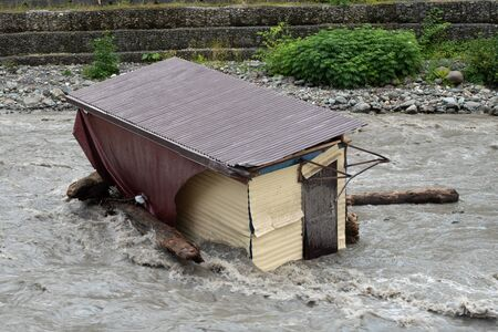 A small house destroyed the mudflow in the mountains. A small house was washed away by a flooded mountain river. The devastating effects of a flood or mudshed. Reklamní fotografie