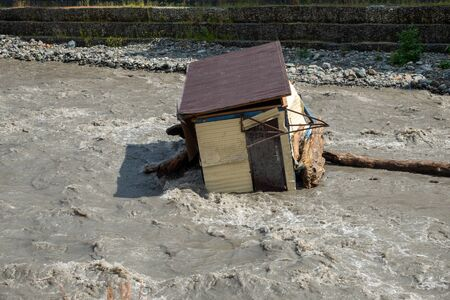 A small house destroyed the mud flow in the mountains. A small house was washed away by a flooded mountain river.