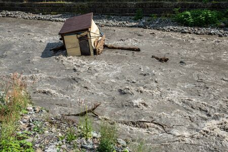 A small house destroyed the mud flow in the mountains. A small house was washed away by a flooded mountain river. The devastating effects of a flood or mushed.