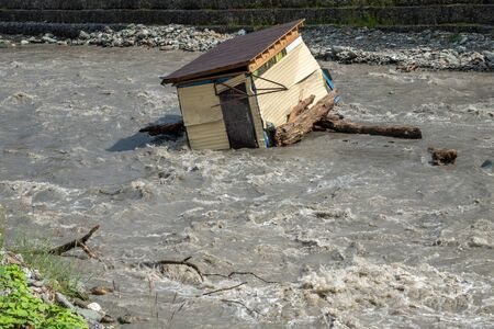 A small house destroyed the mudflow in the mountains. A small house was washed away by a flooded mountain river.