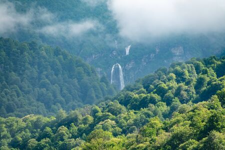 Green mountains with a high waterfall in fog and clouds. Powerful stream of a mountain river among stones and rocks. Banco de Imagens