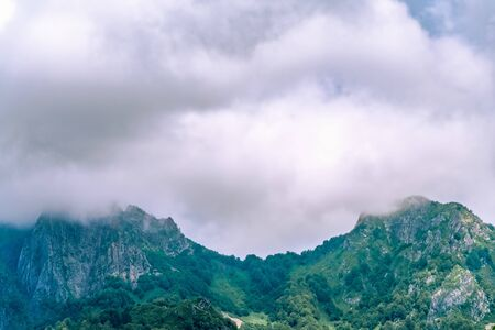 Mountain ranges with green and rocky slopes. Mountains with snowy peaks hidden in the clouds. Thick clouds over the mountain ranges.