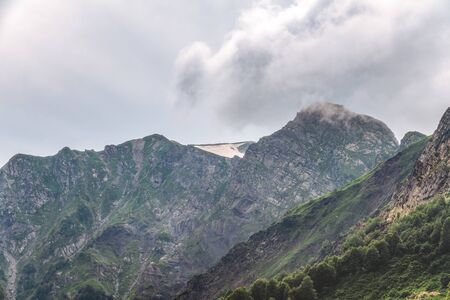 Clouds and fog on the slopes of mountain ranges with snowy peaks in summer. High mountains with green slopes. Фото со стока