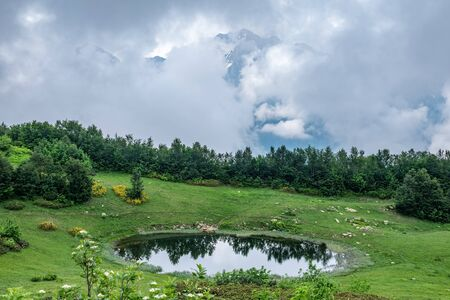 View of a mountain lake with clear water and reflection at cloudy summer day. Caucasus, Russia
