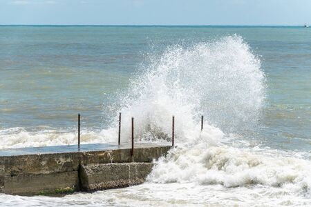 Sea wave with spray during storm at Black sea in Sochi, Russia. Muddy sea waves with foam and spray.
