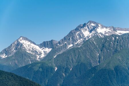 High mountains with green slopes and snowy peaks. Mountain ranges in summer. Stock Photo - 128427490