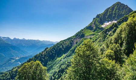 High mountains with green slopes and snowy peaks. Mountain ranges in summer.
