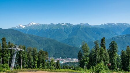 A panoramic view of the Valley with apartment buildings, surrounded by mountains with cable cars. Krasnaya Polyana, Sochi, Caucasus, Russia.