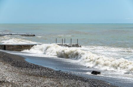 Sea wave with spray during storm at Black sea in Sochi, Russia. Muddy sea waves with foam and spray. Stock Photo
