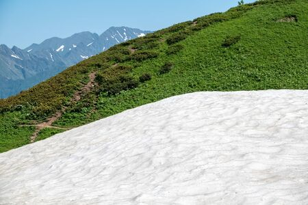 White snow high in the mountains in summer. Summer in the mountains.