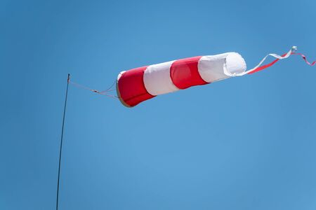 Windsock on a background of blue sky on a sunny day. High wind speed, strong wind. Sky background with copy space.